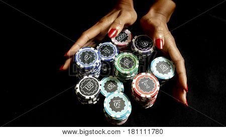 The female poker player with paint red nails pushing her poker chips going all in forward to bet on black fabric gamling and casino concept