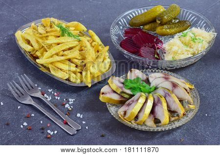 Healthy lunch or dinner with smoked mackerel, pickled cucumbers, beetroot, sauerkraut, french fries on a grey abstract background. Healthy food. Food for fastening