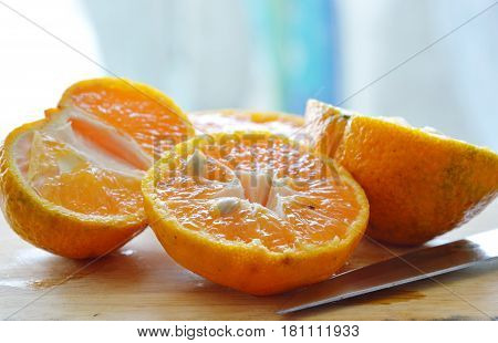 orange cut for squeeze on wooden chop block