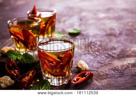 Transparent alcoholic drink with red pepper. Selective focus.