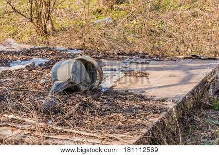 Old rusty watering can laying on makeshift table in a wooded area surrounded by tall grass in shrubs