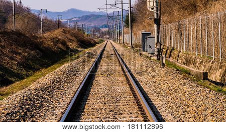 Landscape of railroad tracks running off into the distance with a small community visible on a mountainside in the background