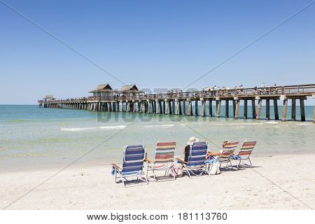 Naples Fl USA - March 18 2017: People enjoying the beautiful white sand beach at the gulf of mexico coast in Naples. Florida United States