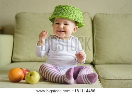 Cheerful baby girl plays with fruits at home. One-year-old child puts a fruit dish on his head.