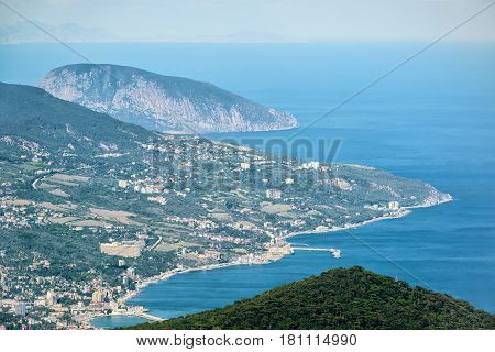 Aerial view of city of Yalta from the Mount Ai-Petri. Ayu-Dag or Bear Mountain in the background. Landscape of Crimea, Russia.