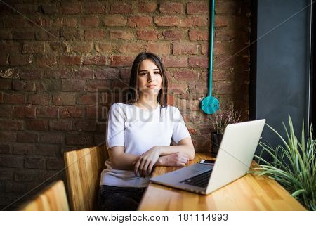 Side view of a young businesswoman using laptop in cafe