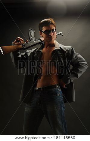 The tough looking guy is holding a rifle.