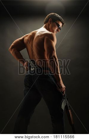 The muscular warrior is looking down with a rifle.