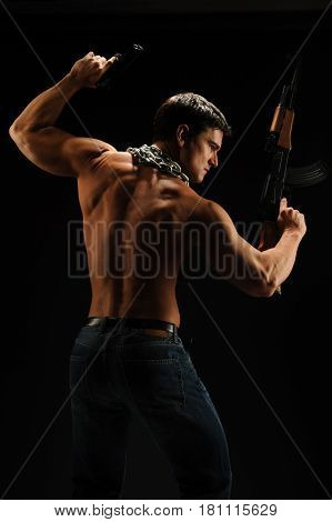 The handsome tough guy is holding a gun.