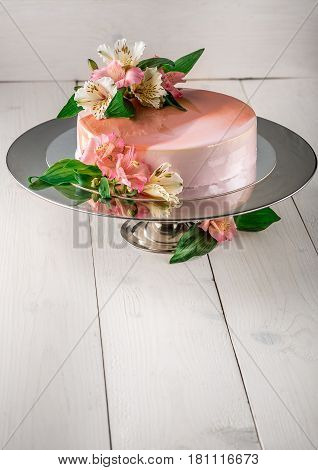 Cake decorated with flowers. Wedding cake on a stand on a white wooden background
