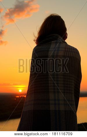 She was impressed at dawn. Silhouette of a girl in a plaid.