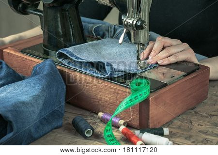 Sewing machine of the past with thread and scissors. The concept of home production and repair of clothing.