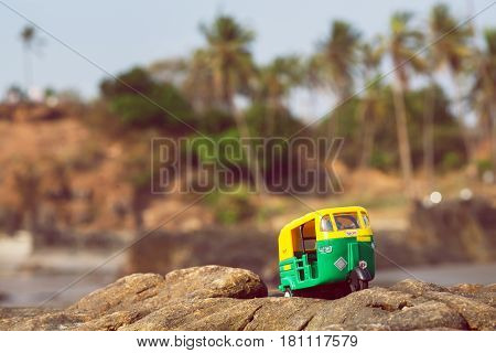 Small model of auto rickshaw vehicle moves across a palm trees beach in India