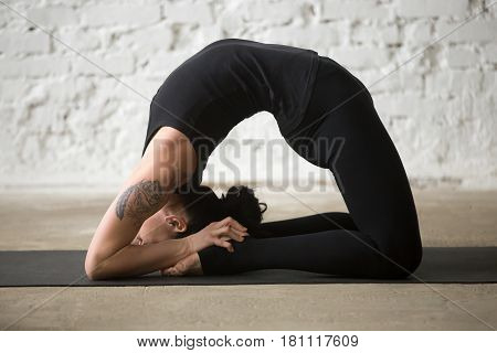 Young yogi attractive woman practicing yoga concept, stretching in Pigeon exercise, Kapotasana pose, working out, wearing sportswear, black tank top and pants, full length, white loft background