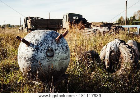 The old naval mine lying on the ground among the trash.