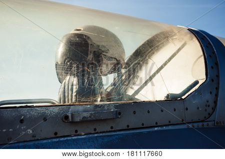 Pilot's old helmet. The fuselage of an old airplane.