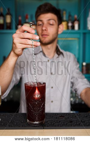 Young handsome barman in bar interior stir ice in red berry alcohol cocktail. Professional bartender at work in night club. Service industry occupation. Vertical image
