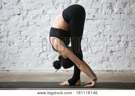 Young yogi attractive woman practicing yoga concept, Standing forward bend, head to knees exercise, uttanasana pose, working out, wearing sportswear, black pants, full length, white loft background