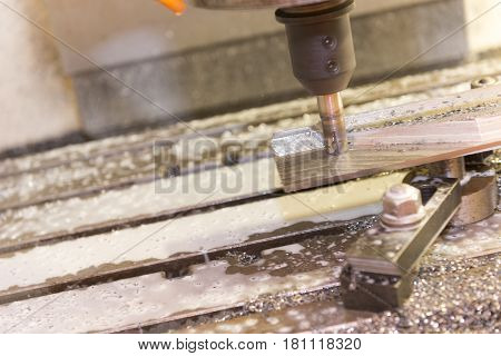 The CNC milling machine cutting the part with the coolant