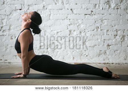 Mid aged yogi attractive woman practicing yoga concept, stretching in upward facing dog exercise, Urdhva mukha shvanasana pose, working out wearing black sportswear, full length, white loft background