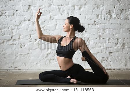 Young yogi attractive smiling woman practicing yoga concept, sitting in One Legged King Pigeon exercise, Eka Pada Rajakapotasana pose, working out, wearing sportswear, full length, white background