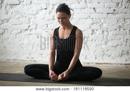 Young yogi attractive woman practicing yoga concept, sitting in Butterfly exercise, baddha konasana pose, working out, wearing sportswear, black tank top and pants, full length, white loft background