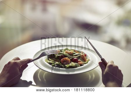 Salad of shrimp in a plate and cutlery in women's hands