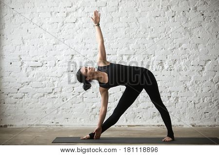 Young yogi attractive woman practicing yoga concept, standing in Utthita Trikonasana exercise, extended triangle pose, working out, wearing sportswear, black pants, full length, white loft background