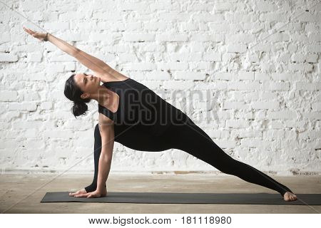 Young yogi attractive woman practicing yoga concept, standing in Utthita parsvakonasana exercise, Extended Side Angle pose, working out, wearing black sportswear, full length, white loft background