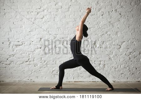 Young yogi attractive woman practicing yoga concept, standing in Warrior one exercise, Virabhadrasana I pose, working out, wearing sportswear, black tank top and pants, full length, loft background