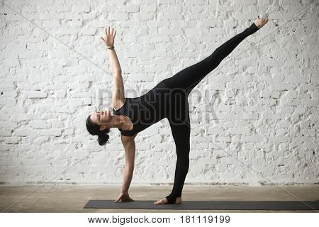 Young yogi attractive woman practicing yoga concept, standing in Half Moon exercise, Ardha Chandrasana pose, working out, wearing sportswear, black tank top and pants, full length, white background