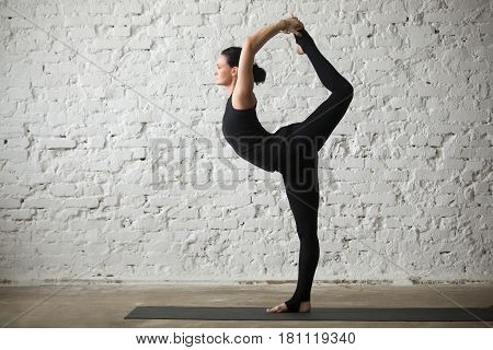 Young yogi attractive woman practicing yoga concept, standing in Natarajasana exercise, Lord of the Dance pose, working out, wearing sportswear, black tank top and pants, full length, loft background