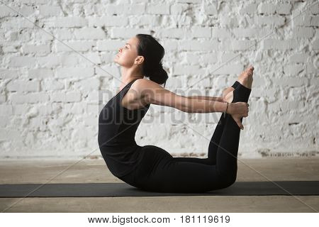 Young yogi attractive woman practicing yoga concept, stretching in Dhanurasana exercise, Bow pose, working out, wearing sportswear, black tank top and pants, full length, white loft background