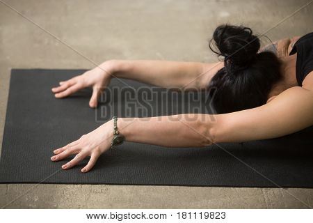 Young yogi attractive woman practicing yoga concept, sitting in Child exercise, Balasana pose, working out, full length, white loft background, close up of arms on black mat