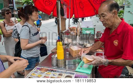 SINGAPORE - MAR 21 2017 : Unidentified man sells ice cream sandwich wafer in front of main shopping mall the popular place for shopping at Orchard Road Singapore.