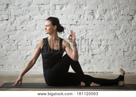 Middle aged yogi smiling woman practicing yoga concept, sitting in Ardha Matsyendrasana exercise, Half lord of the fishes pose, working out wearing black sportswear, full length, white loft background