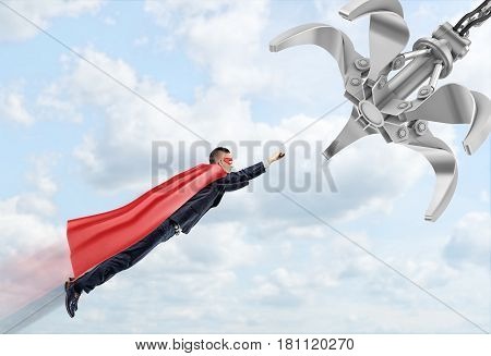 A businessman wearing a red superhero cape flying through the clouds following a robotic manipulator. Business goals. Rewards for risk. Business and innovation.