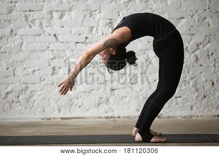 Young yogi attractive woman practicing yoga concept, standing Backward Bend exercise, Ardha Chakrasana pose, working out, wearing sportswear, black tank top and pants, full length, white background