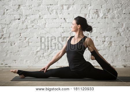 Middle aged yogi attractive woman practicing yoga concept, stretching in Monkey God exercise, Splits, Hanumanasana pose, working out wearing sportswear, black pants, full length, white loft background