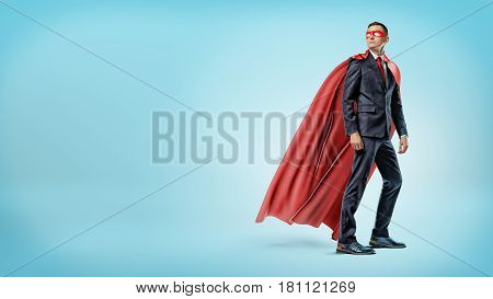 A businessman in a flowing red superhero cape and a mask looking over his shoulder on blue background. Business hero. Business and success. Superpowers.