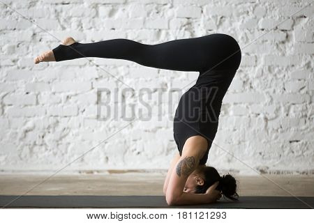 Young yogi attractive woman practicing yoga concept, standing in headstand exercise, variation of salamba sirsasana pose, working out, wearing black sportswear, full length, white loft background