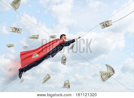 A businessman wearing a red superhero cape flying through the clouds following a dollar bill. Business goals. Impossible results. Earning and investment.