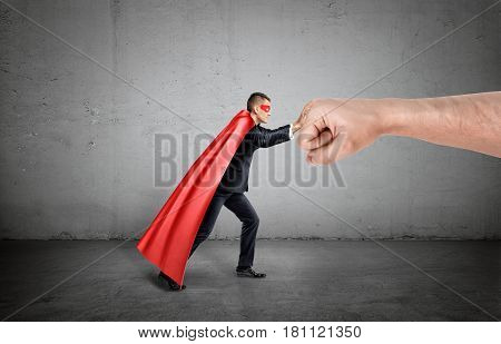 A businessman in a red cape and a mask pushing at a giant human fist on concrete background. Winning and losing. Effort and results. Inhuman strength.