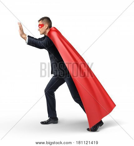 A businessman in a superhero red cape and an eye mask pushing on an invisible object in side view. Problems and obstacles. Business and competition. Overcoming difficulties.