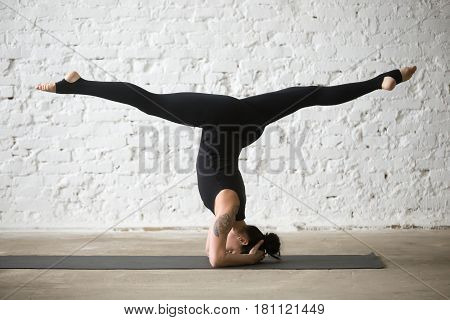 Young yogi attractive woman practicing yoga, doing variation of supported headstand exercise with splits legs, salamba sirsasana pose, working out wearing black sportswear, white loft background