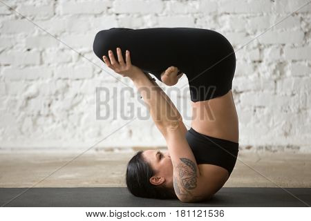 Young yogi attractive woman with tattoo practicing yoga concept, Urdhva Padmasana Upward Lotus in shoulderstand exercise, working out wearing black sportswear pants, full length, white loft background