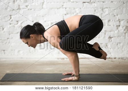 Mid aged yogi attractive woman practicing yoga concept, standing in Bakasana exercise, Crane pose, working out wearing black sportswear tank top and pants, full length side view, white loft background