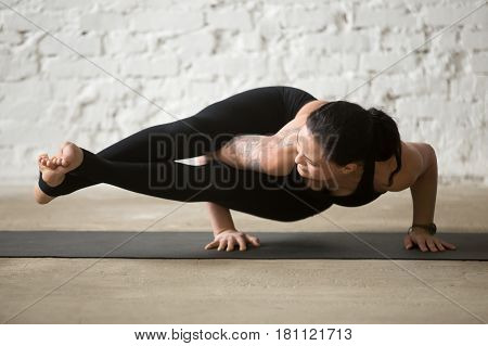 Middle aged yogi attractive woman practicing yoga concept, standing in Astavakrasana exercise, Eight Angle pose, working out wearing black sportswear pants, full length, white loft background