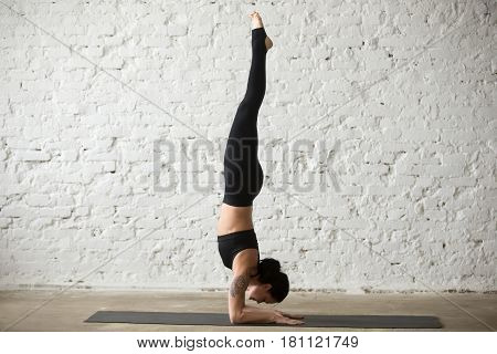 Middle aged yogi woman practicing yoga concept, standing in Pincha Mayurasana exercise, handstand pose, working out, wearing sportswear, black tank top, pants, full length, white loft background