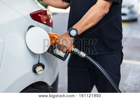 Car refueling on petrol station. Man pumping gasoline oil.